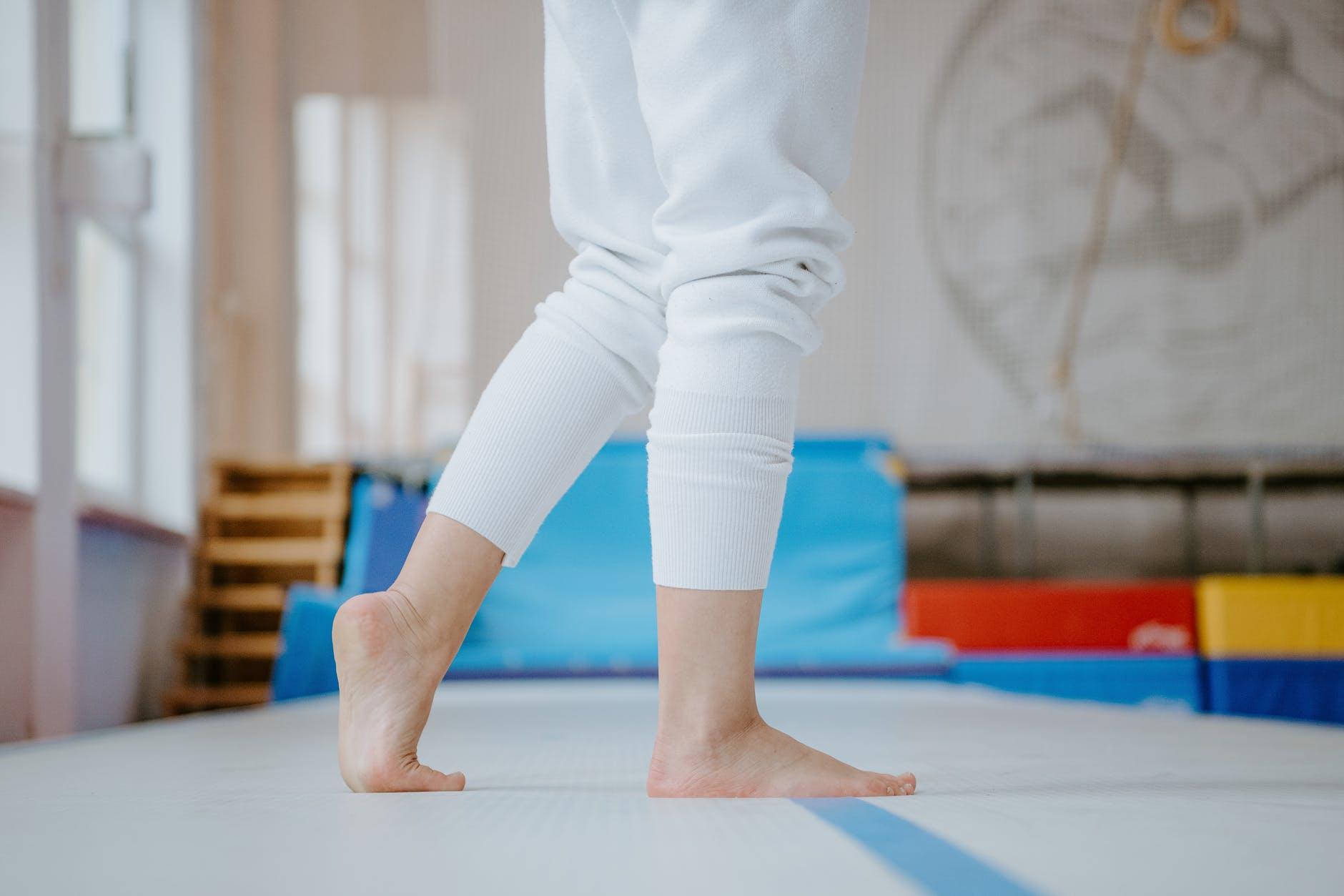 crop female athlete standing on mat in gymnastic studio