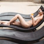 young slim woman lying on sunbed and enjoying refreshing drink