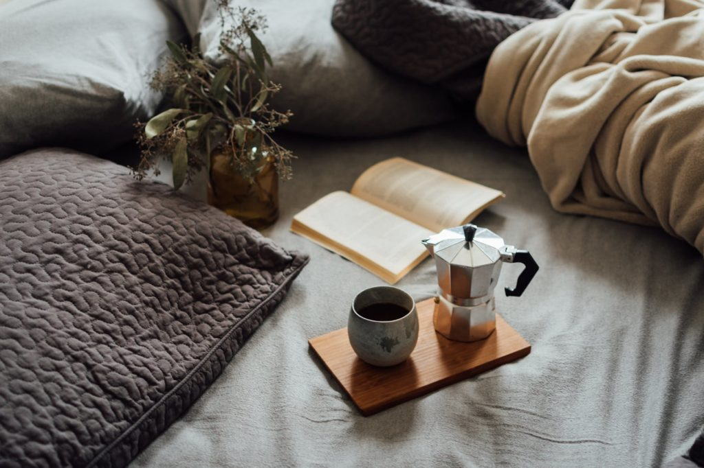 coffee and book on comfortable bed