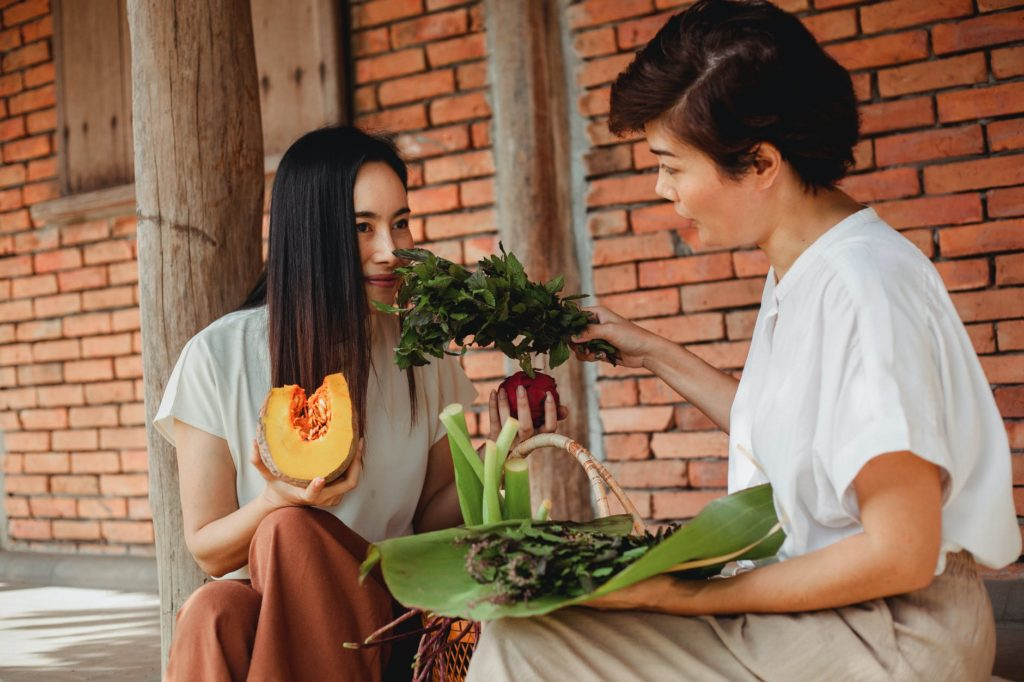 asian woman smelling green leaves sitting on street
