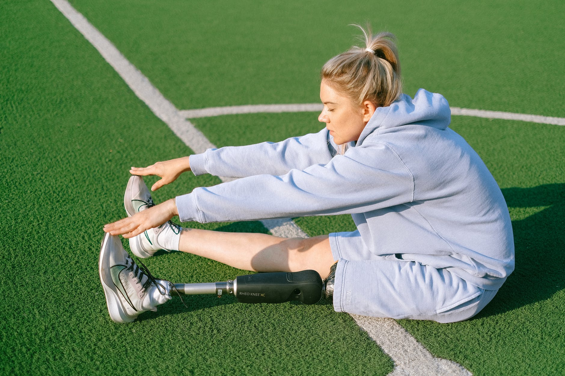 focused disabled woman stretching body on stadium