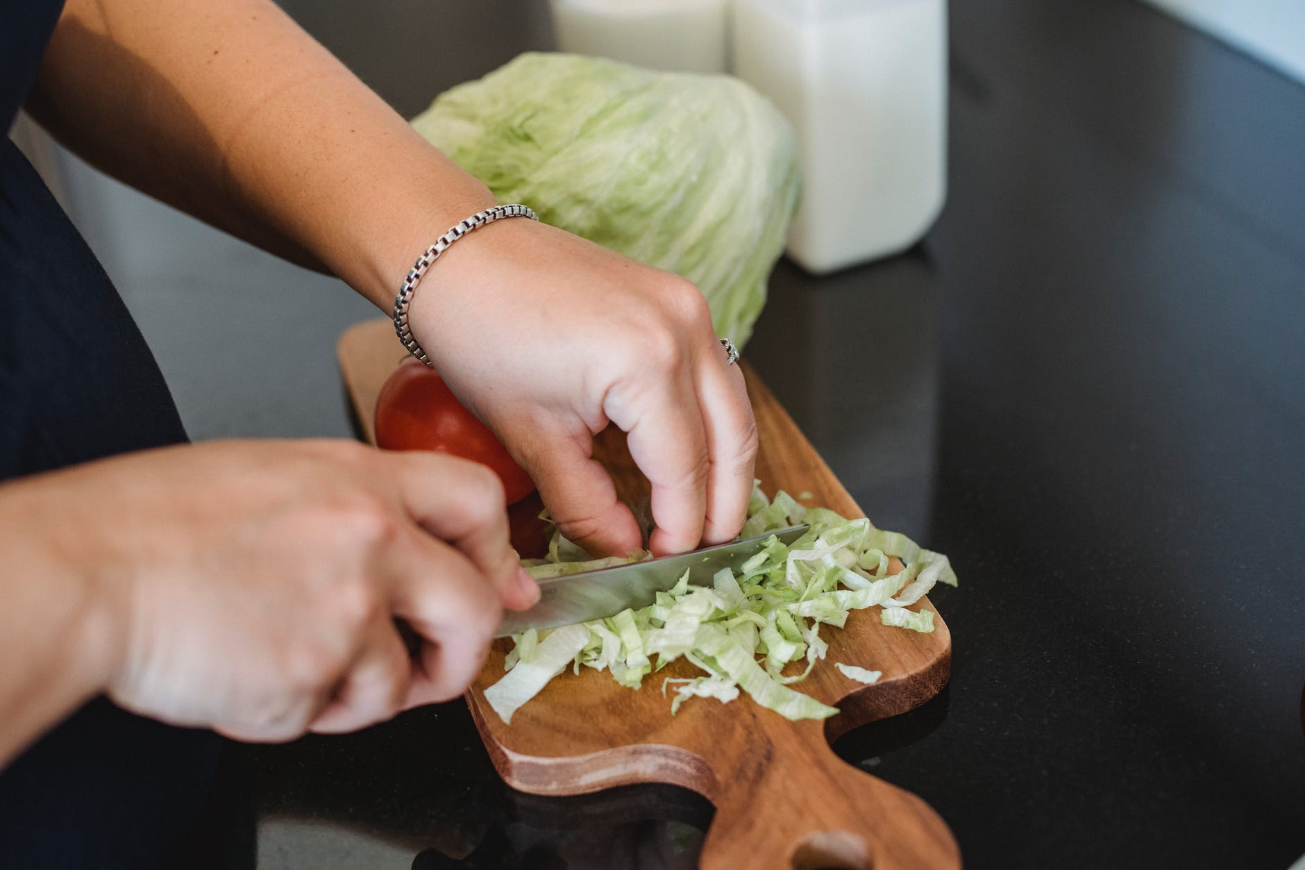 female chopping lettuce leaves for salad