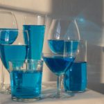 glasses with blue absinthe drink on table