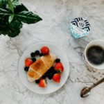 breakfast with berries and croissant with yogurt and coffee