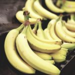 selective focus photo of bunch of bananas on black surface