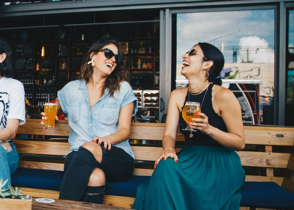 two smiling women sitting on wooden bench