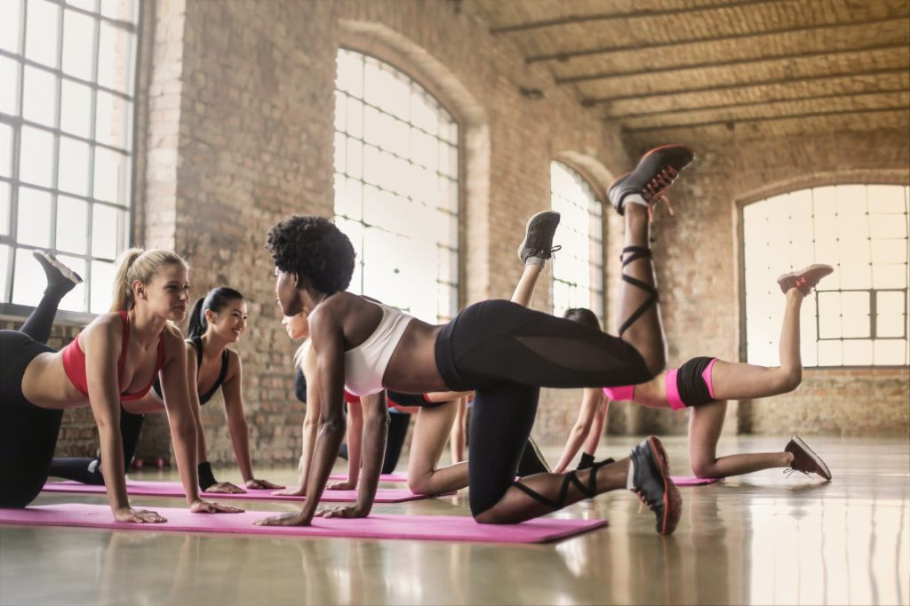 women doing yoga class on pink yoga mat