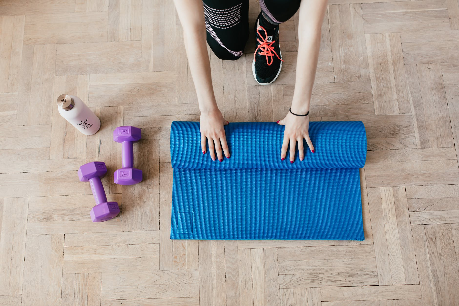 crop sportswoman unfolding sport mat on wooden floor