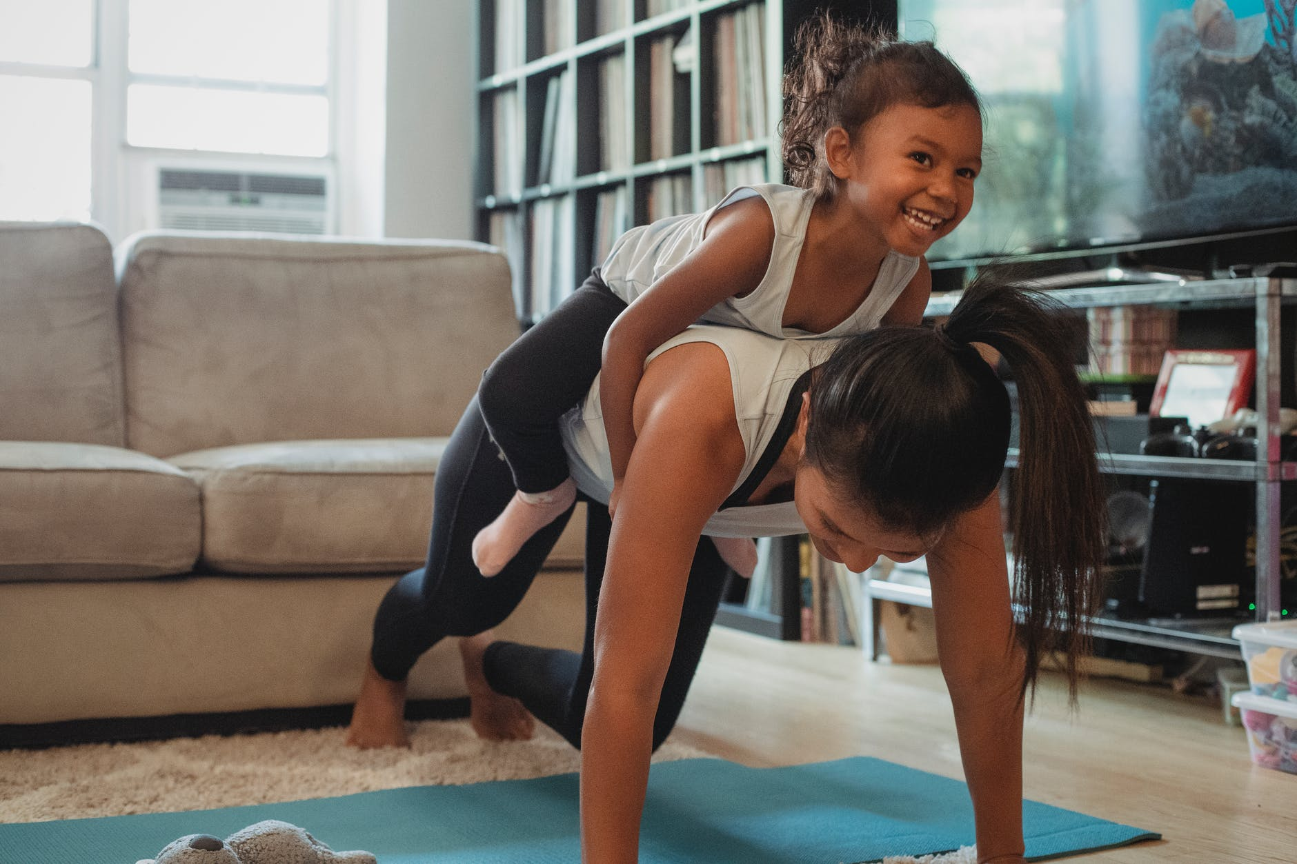 young asian woman piggybacking smiling daughter while exercising at home