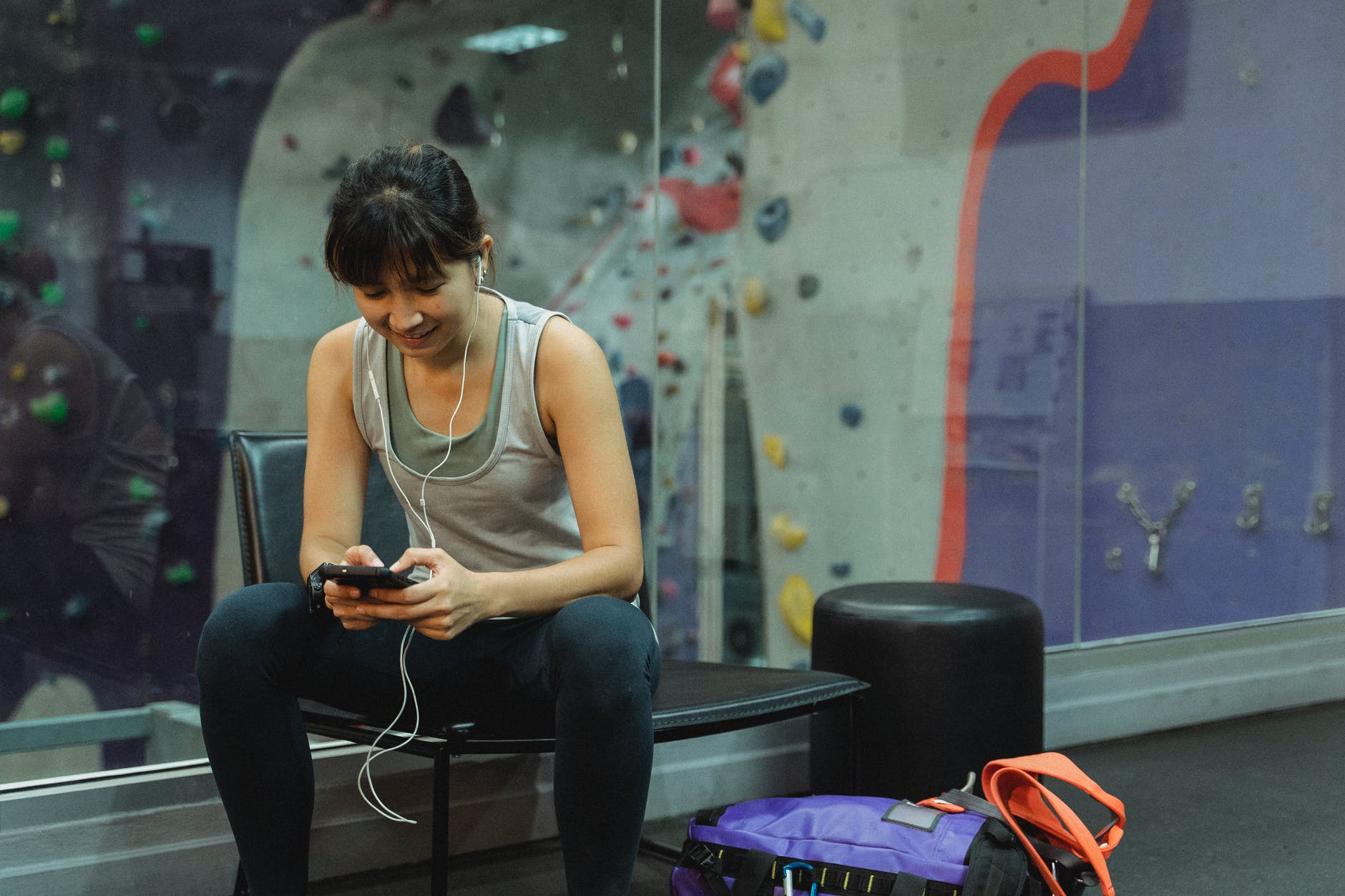 positive young asian woman using smartphone while resting after training in gym