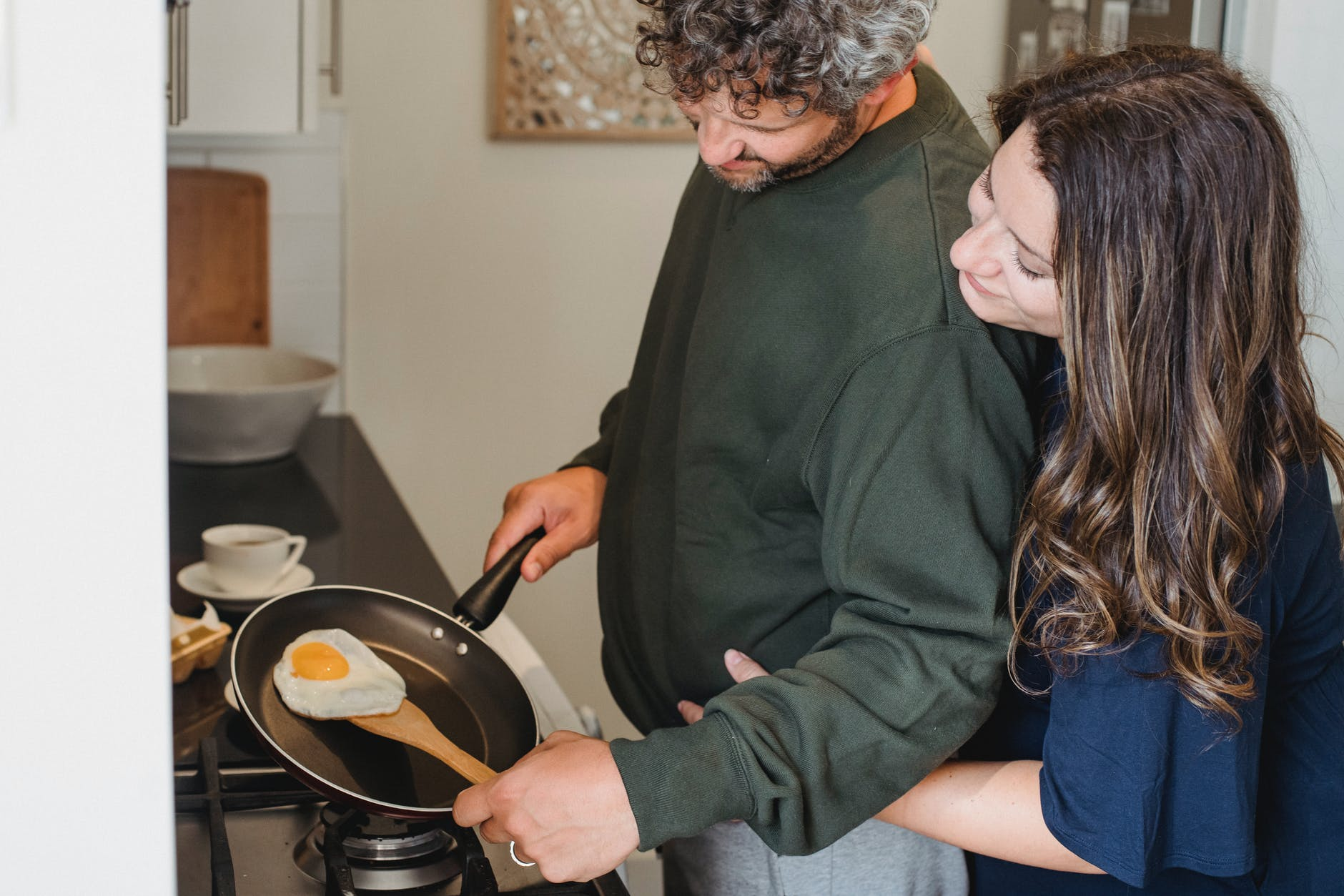 cheerful couple hugging while cooking egg for breakfast