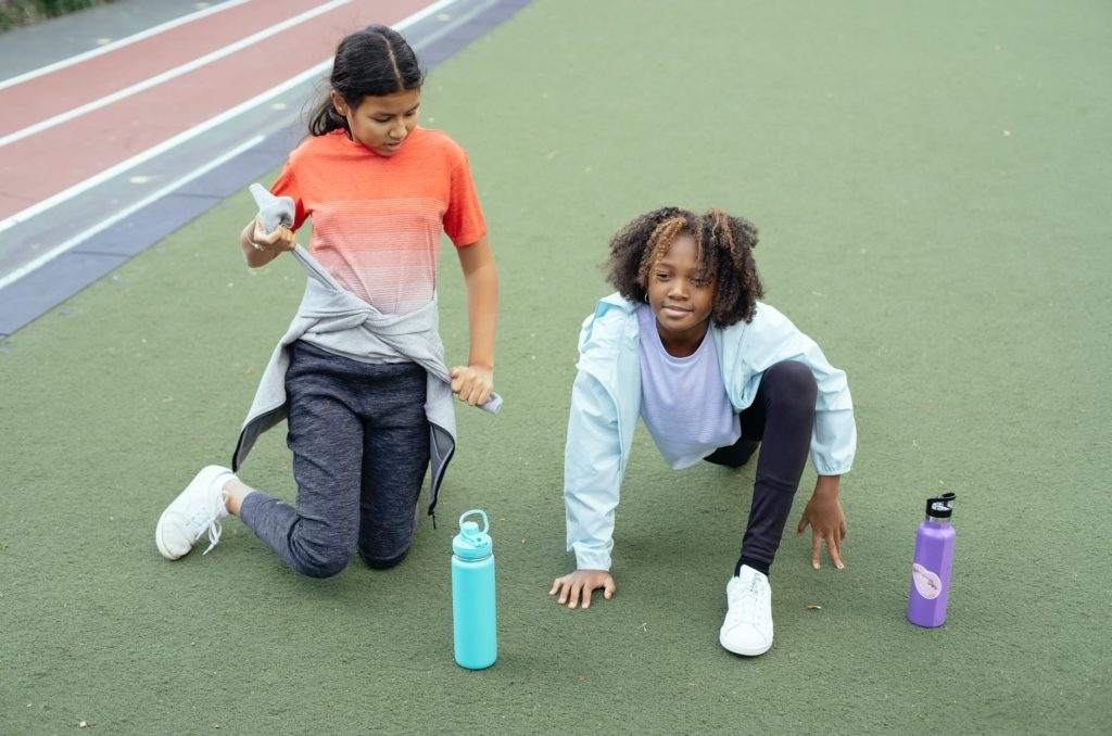 smiling black girl stretching before training with friend on running track