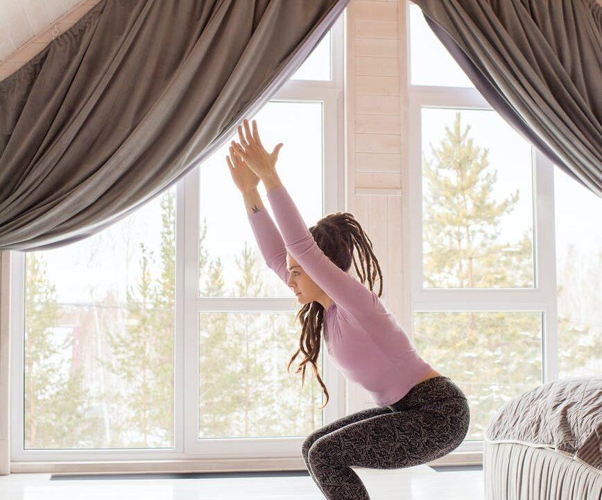 woman in gray leggings and purple long sleeves doing yoga