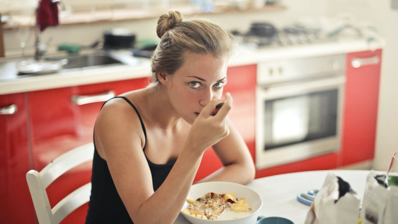 woman in black tank top eating cereals