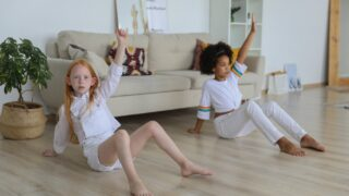 adorable diverse girls training together on floor