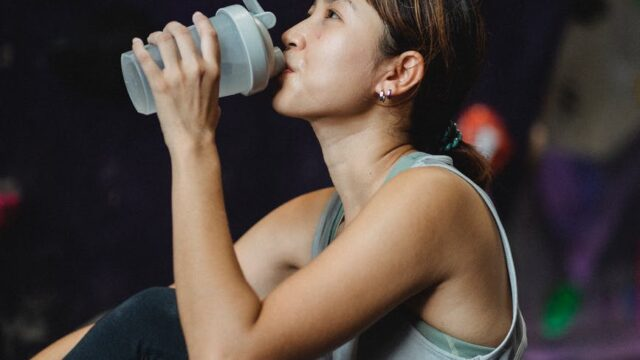 thirsty ethnic sportswoman drinking water after bouldering workout