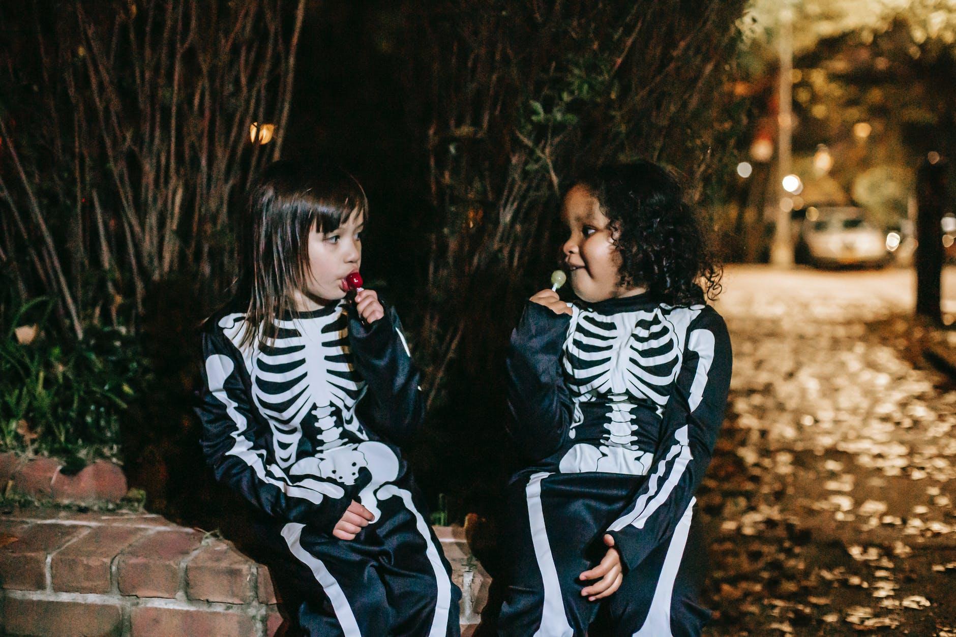 multiethnic girlfriends eating tasty lollipops in park on halloween night