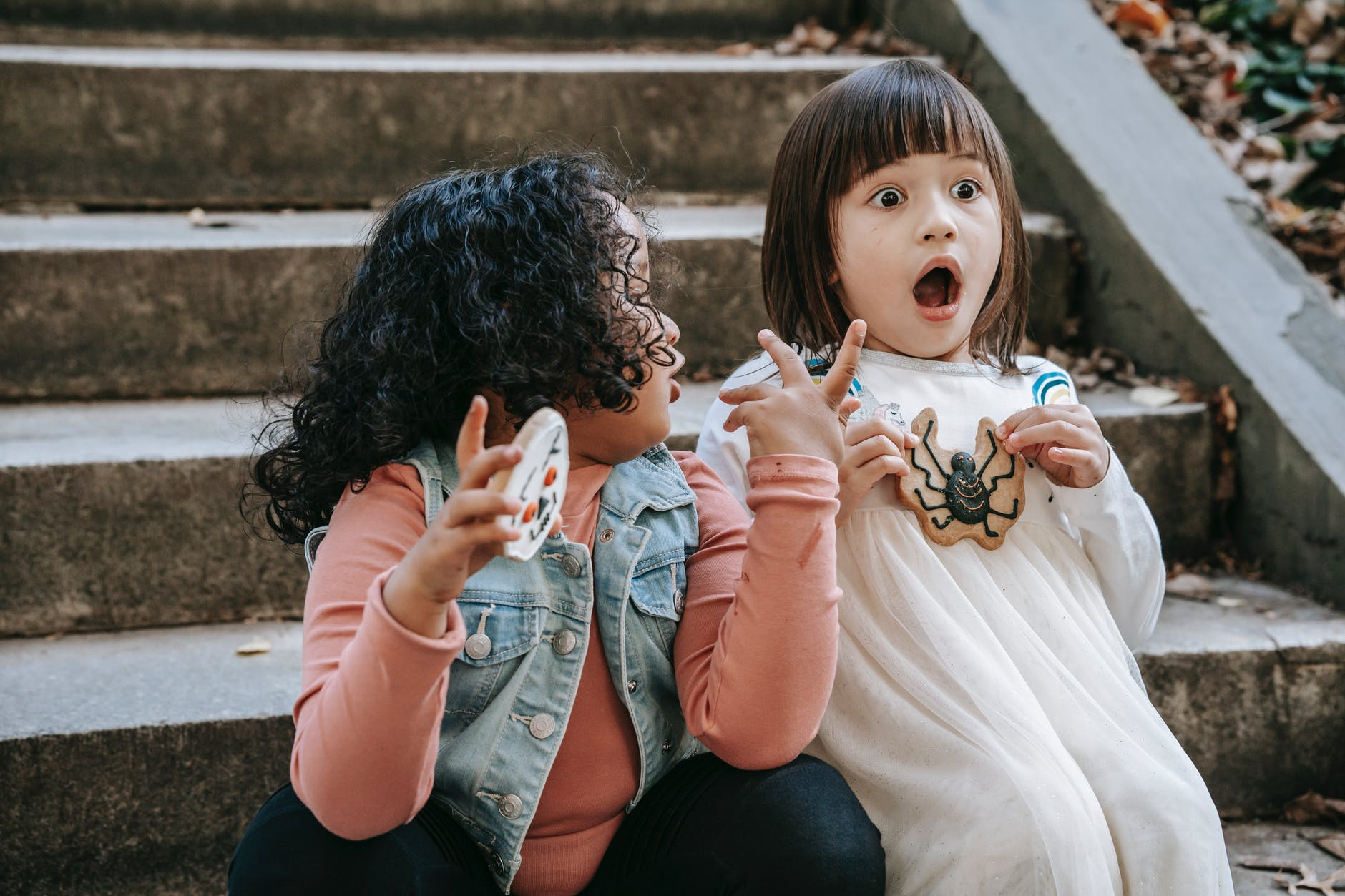 amazed diverse girls with halloween gingerbread cookies sitting on staircase