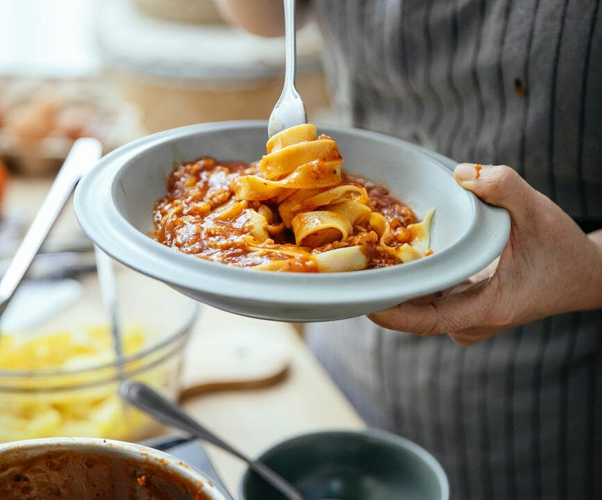 crop woman with delicious pasta in plate