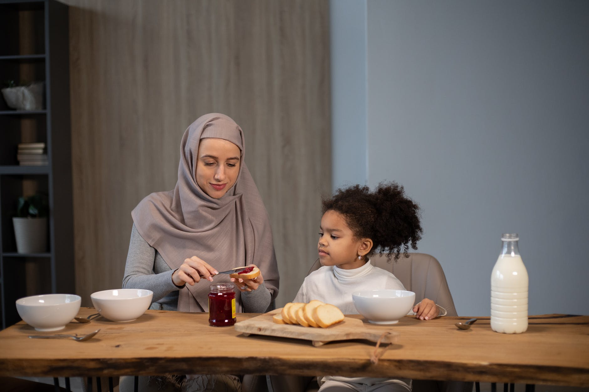 diverse mother and daughter at table having breakfast