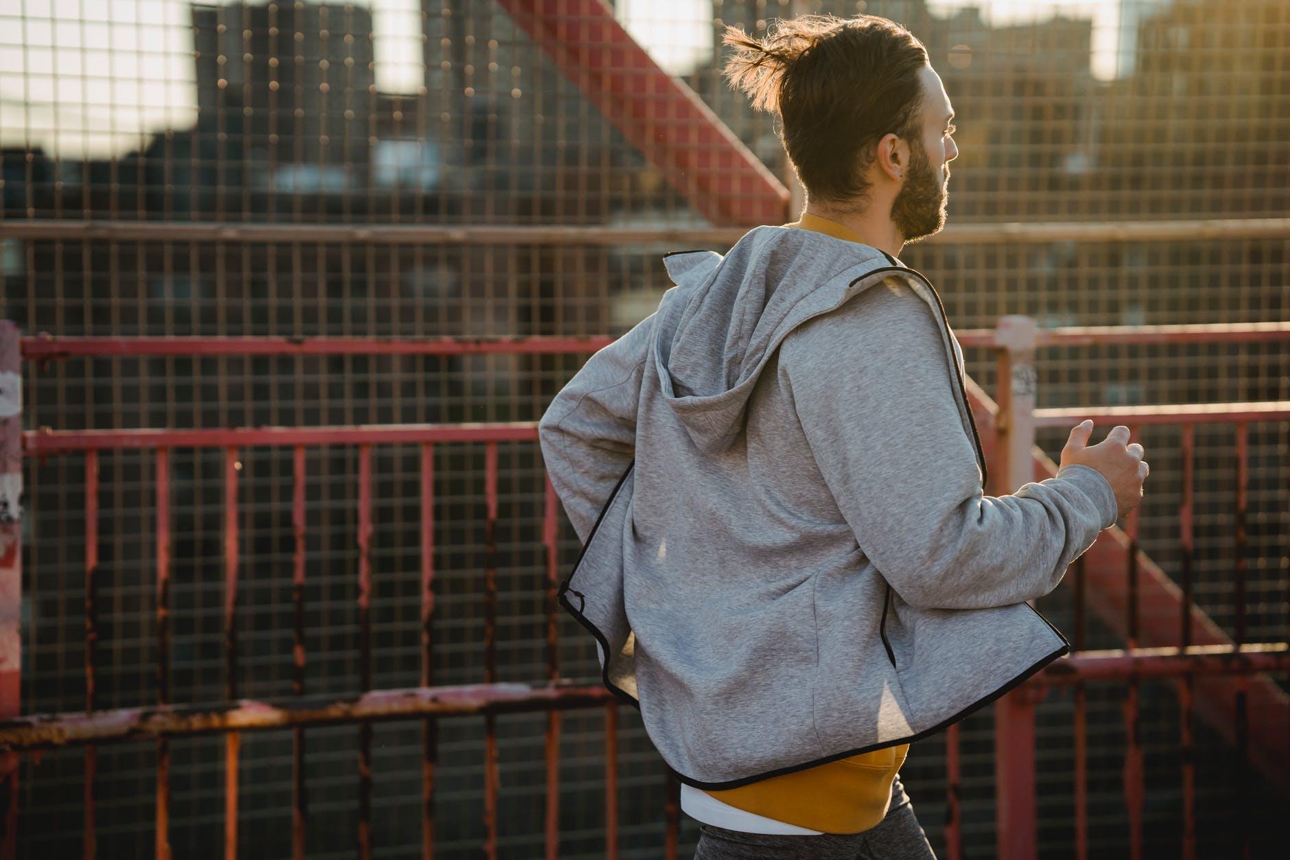 hipster runner jogging on urban bridge during workout