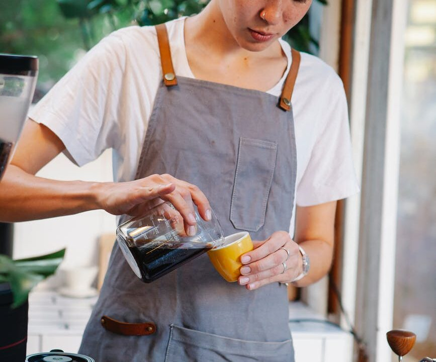 woman pouring fresh aromatic coffee from jug into cup