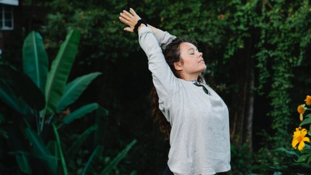 woman with eyes closed stretching among green tropical trees