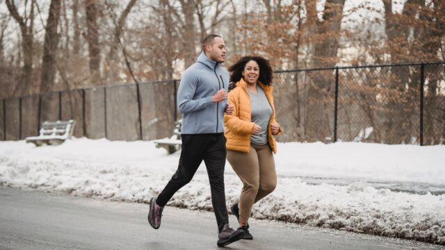 ethnic trainer and woman jogging on snowy street