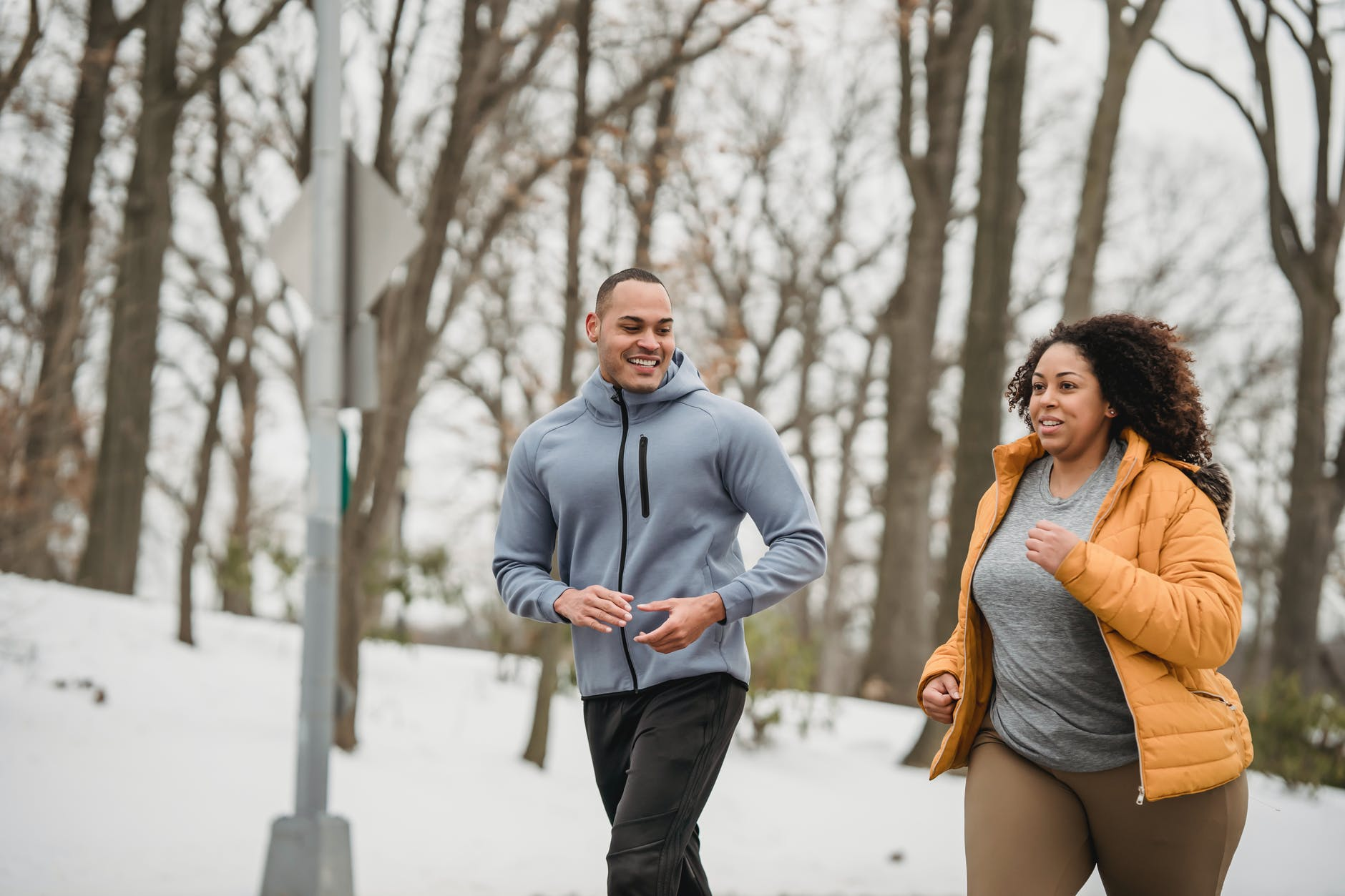 diverse fit man and plump female running in snowy park