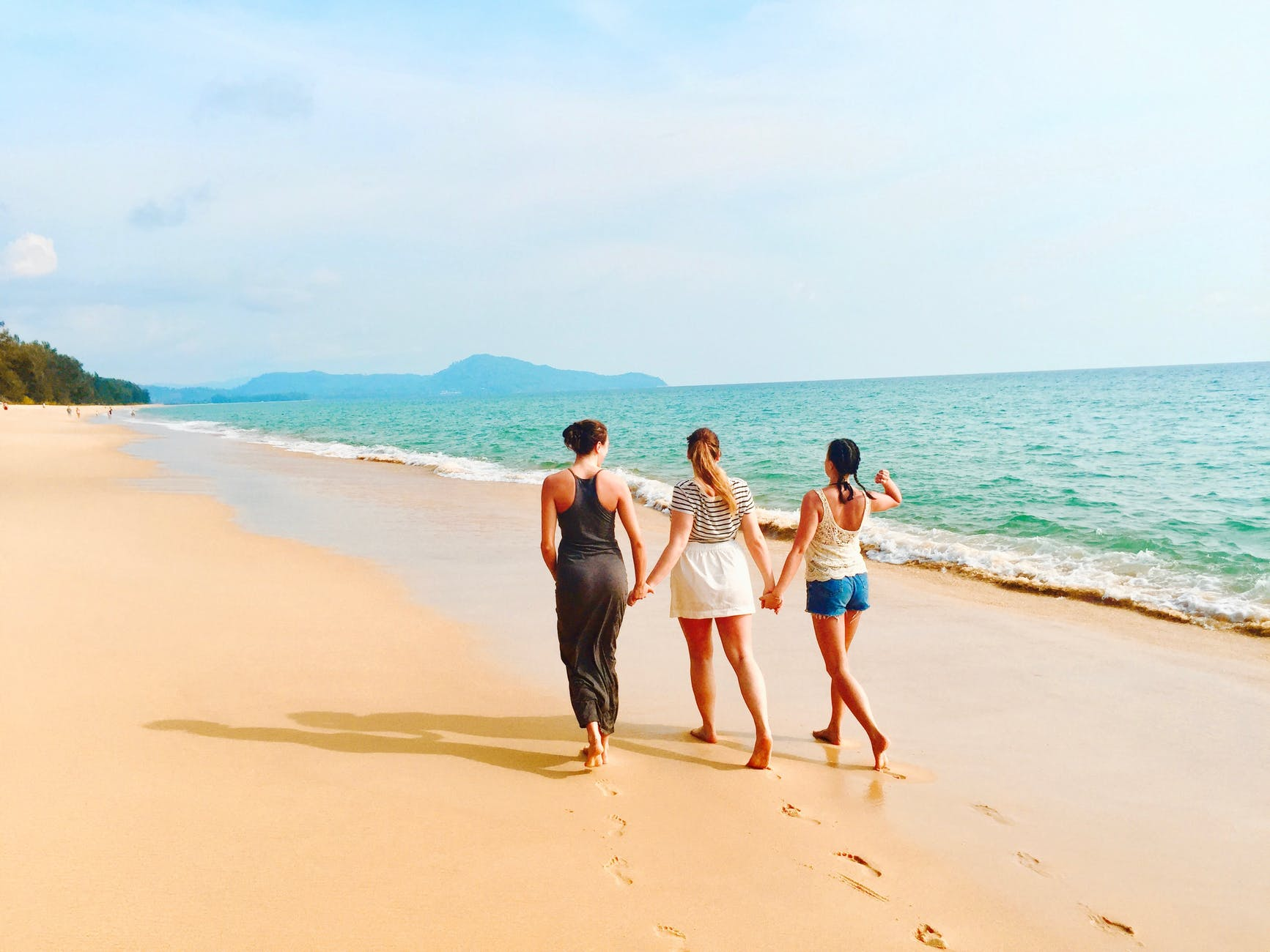 three women walking on seashore under blue sky