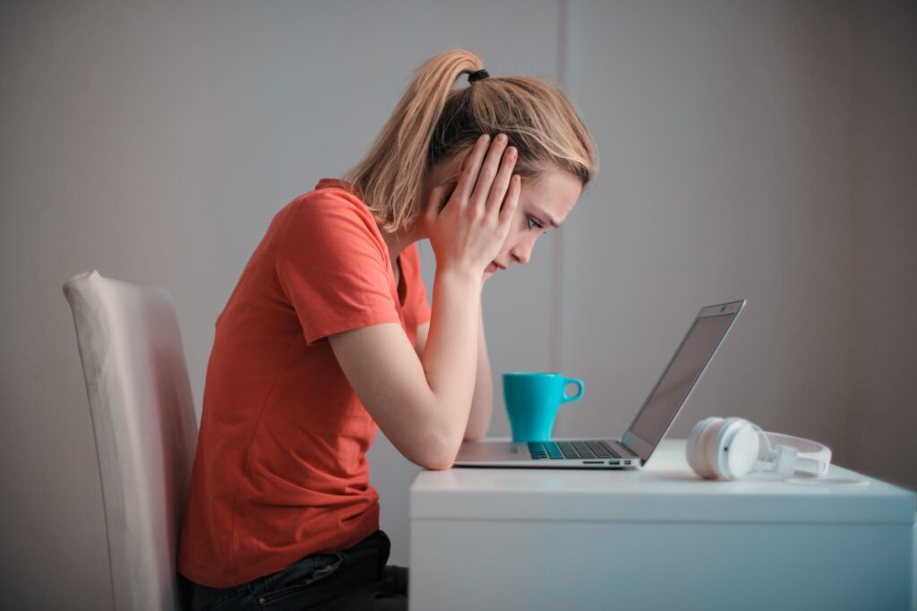young troubled woman using laptop at home