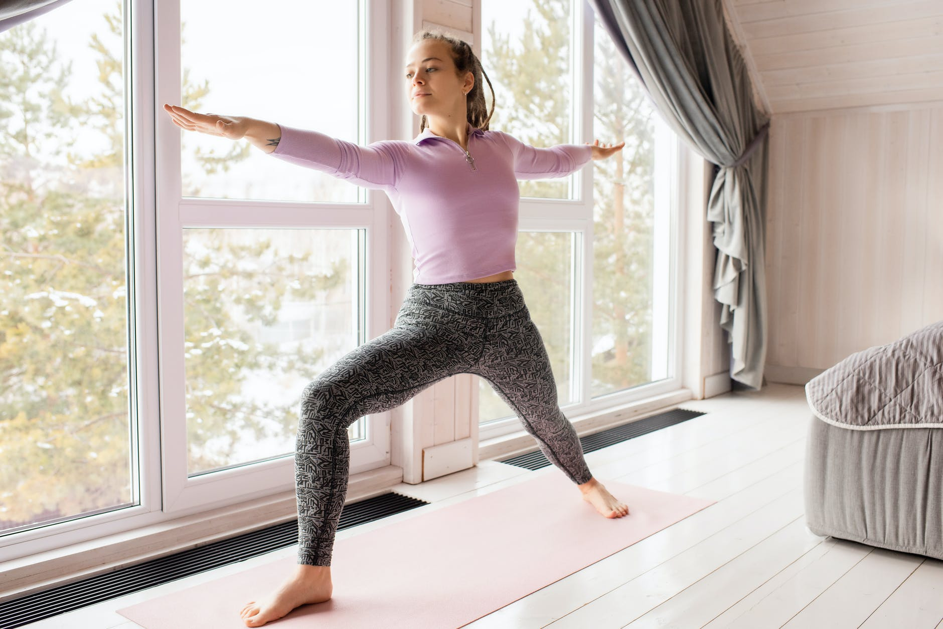 woman in pink long sleeve shirt and gray leggings doing yoga