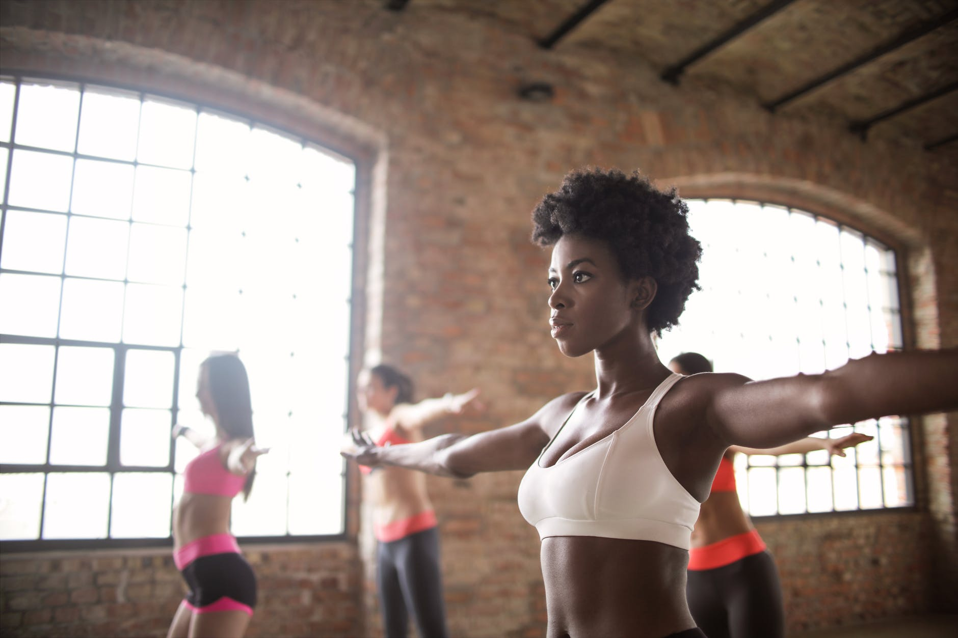 confident fit ethnic woman training with other sportswomen in modern fitness studio