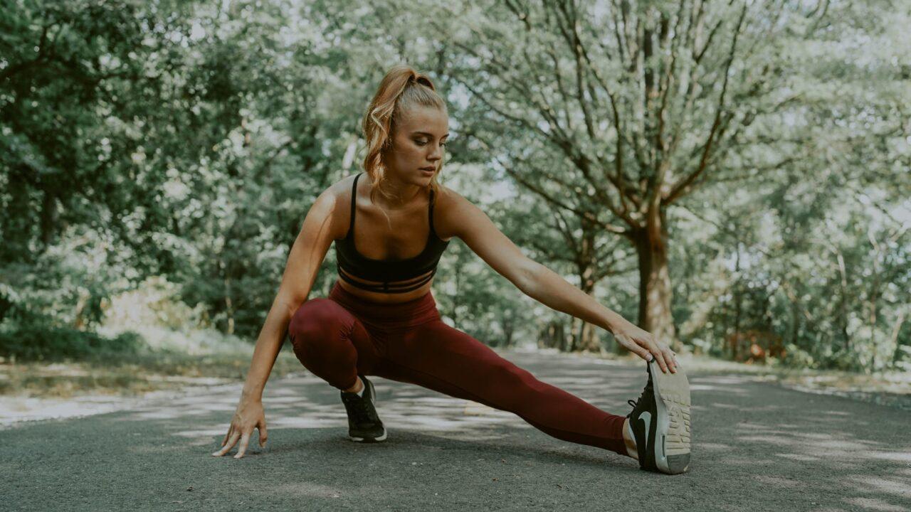 flexible sportswoman doing lunges forward exercise
