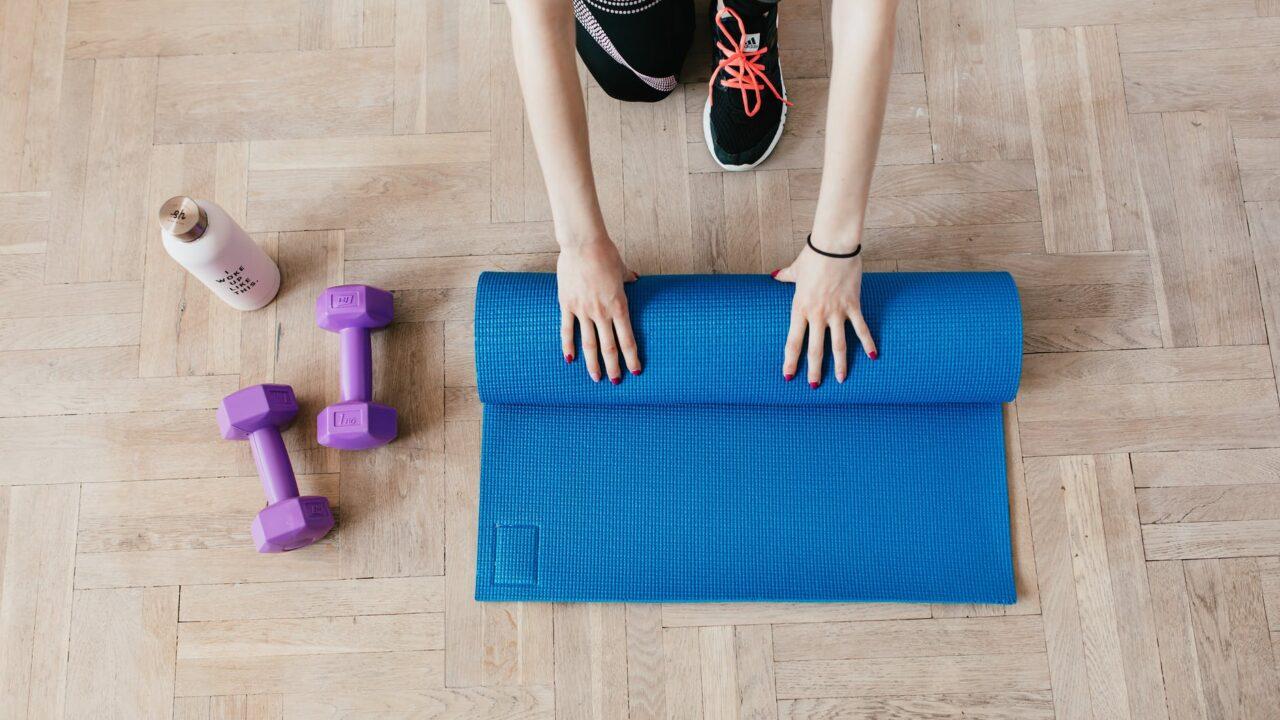 crop sportswoman unfolding sport mat on wooden floor