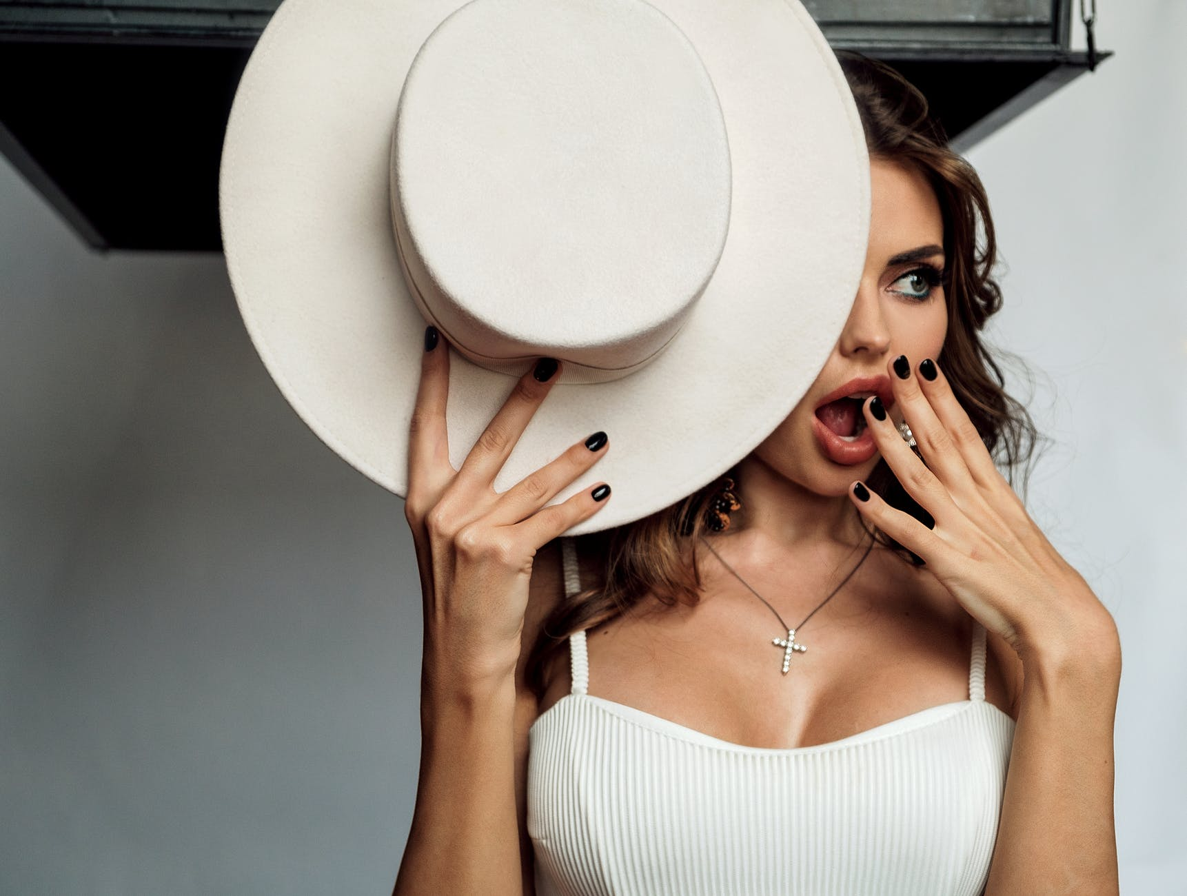 stylish woman with hat standing near white wall