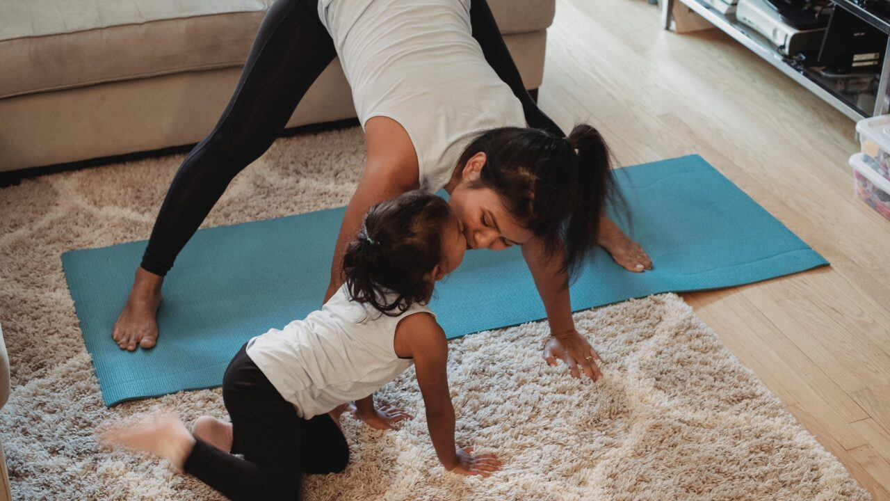 asian mother stretching body and kissing cute daughter at home
