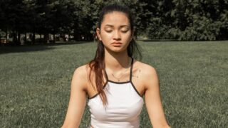 flexible woman practicing yoga in park