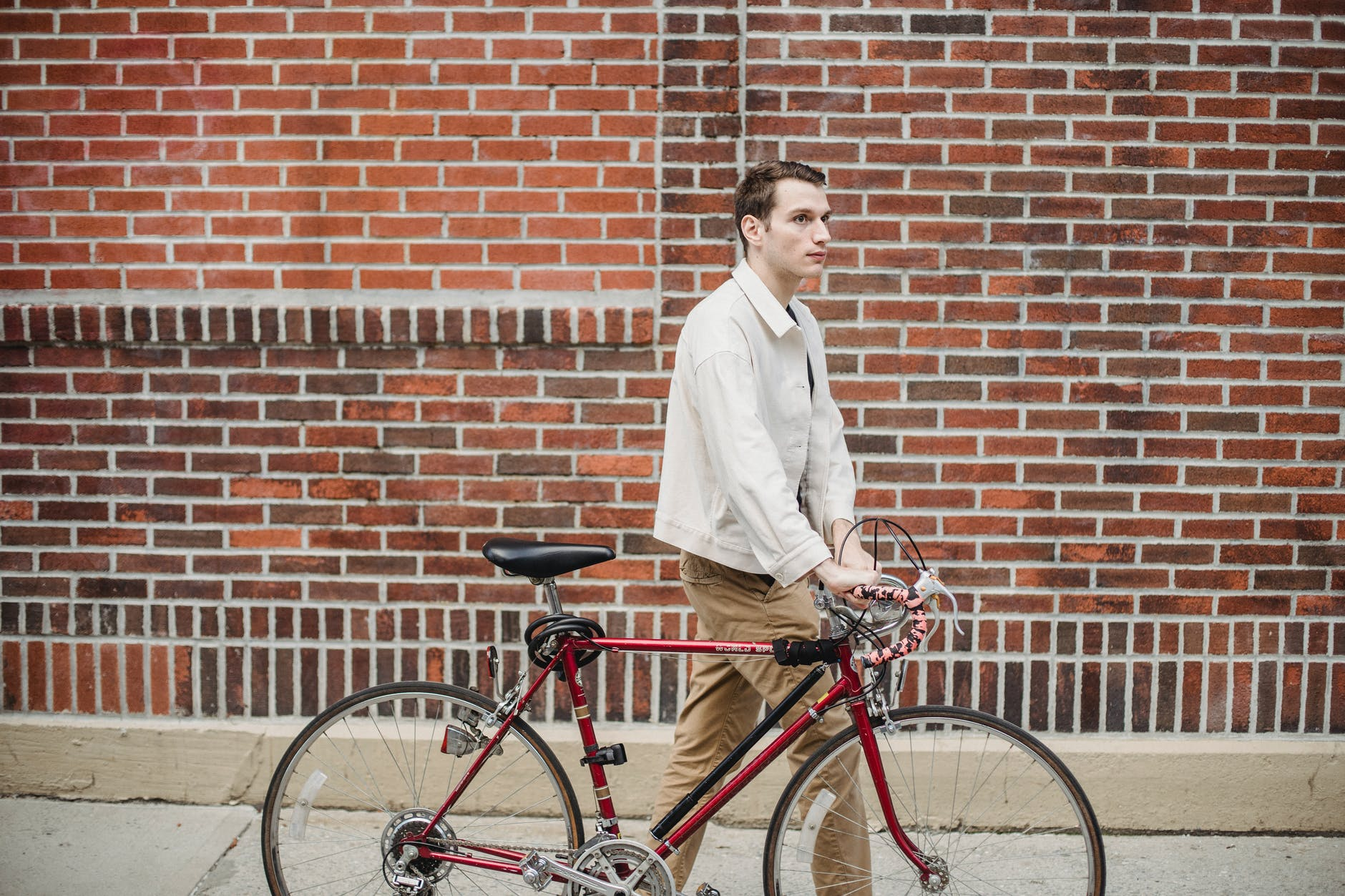 young calm man rolling bicycle on city street