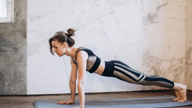 woman in black tank top and black leggings doing yoga