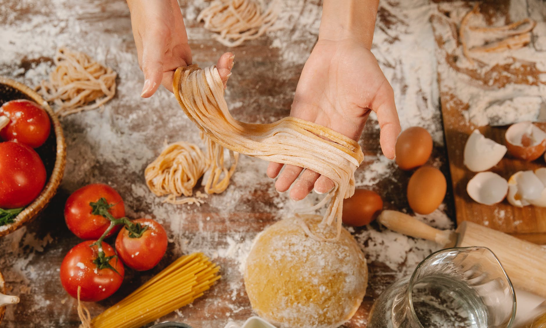 woman showing spaghetti with flour and dough