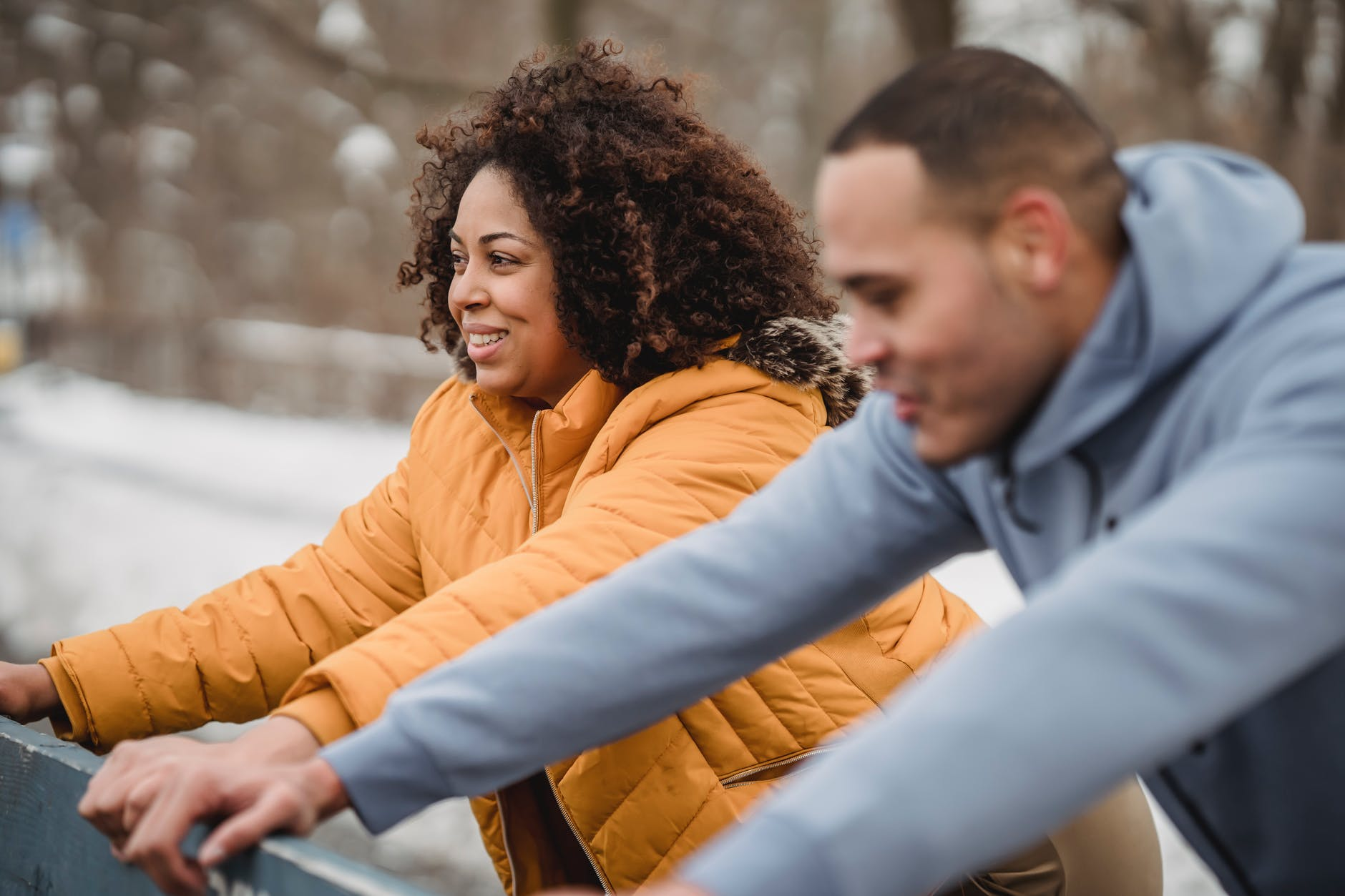 cheerful black couple warming up in park